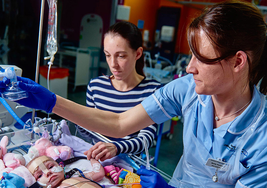 A nurse and a parent caring a for child on PICU