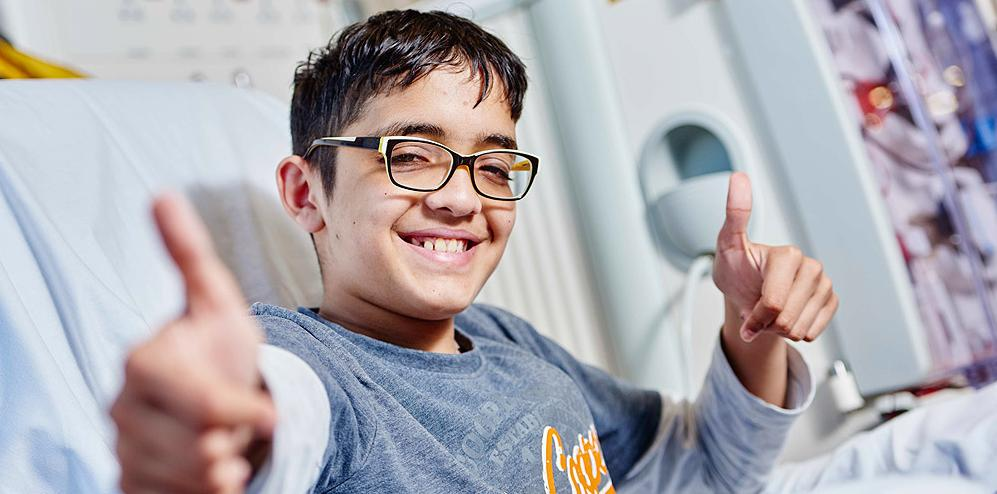 Teenager in a hospital bed smiling and pointing towards the camera